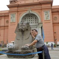 A tourist poses for a picture next to a statue in front of the Egyptian Museum in Tahrir Square in Cairo on April 19. | REUTERS