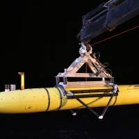 The Phoenix Autonomous Underwater Vehicle Artemis is hoisted onto the Australian vessel Ocean Shield on April 17 after completing a mission in the search for missing Malaysia Airlines Flight MH370 in the southern Indian Ocean. | AFP-JIJI