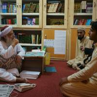 Maulana Abdul Aziz (left), head cleric of a Pakistani seminary, talks to visitor in a library named after slain al-Qaida leader Osama bin Laden, on Friday in Islamabad. | AP