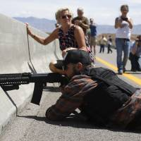 A protester aims his weapon from a bridge next to the Bureau of Land Management's base camp where seized cattle that belonged to rancher Cliven Bundy were being held near Bunkerville, Nevada, on Saturday.   REUTERS