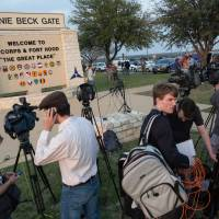 Members of the media wait outside an entrance to the Fort Hood military base for updates on a shooting that occurred inside on Wednesday.   AP