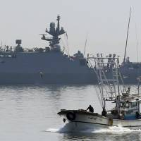 A fishing boat sails past a South Korean naval vessel in the sea off Daecheongdo Island, near the border with North Korea, on Tuesday. Seoul said the same day that an unmanned drone that crashed on Baengnyeong Island, near the disputed maritime border, was recovered after the two nations fired hundreds of artillery rounds into nearby waters. | REUTERS