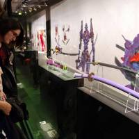 Women look at traditional Japanese swords and replicas of blades that appeared in the animated series 'Neon Genesis Evangelion' Tuesday in Paris at a preview of an exhibition that opened Wednesday. | KYODO
