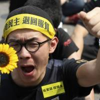 A demonstrator shouts slogans in front of the Presidential Office in Taipei on March 30. Thousands of demonstrators have marched the streets in recent weeks to protest a controversial trade pact with mainland China — a deal that opposition leaders say will disadvantage Taiwan and leave it vulnerable to Chinese encroachment. | REUTERS