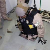 This image provided by the U.S. Immigration and Customs Enforcement agency shows an agent examining one of two tunnels discovered Tuesday in San Diego's Otay Mesa industrial park. | AP