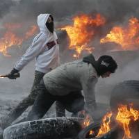 Protesters throw Molotov cocktails at riot police during clashes in central Kiev on Jan. 25. | AP