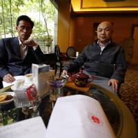 A paper with the verdict in the trial of Chinese rights activist Xu Zhiyong is seen on a table as Xu's lawyers Zhang Qingfang (right) and Liu Shuqing speak to journalists at a hotel in Beijing on Friday. The prominent Chinese rights activist expressed defiance Friday after a court upheld his four-year jail sentence, saying the pall of communism and dictatorship would eventually give way to freedom and justice. | REUTERS