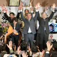 Former Kagoshima Prefectural Assembly chief Masuo Kaneko (center) cheers with supporters Sunday after projections declared him the winner of the House of Representatives by-election in Kagoshima Prefecture on Sunday. | KYODO