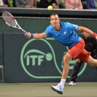 Playing the angles: Lukas Rosol of the Czech Republic reaches for a return against Japan's Yasutaka Uchiyama during their men's singles match at the Davis Cup World Group quarterfinals on Sunday at Ariake Colosseum. Rosol defeated Uchiyama 6-3, 3-6, 6-4. | AFP-JIJI