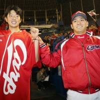Bursting on the scene: Carp rookies Daichi Osera (left) and Kosuke Tanaka pose for photos after Hiroshima's 9-2 win over Tokyo Yakult on Thursday night at Jingu Stadium. | KYODO