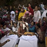 Pakistani women grieve over the coffins of their relatives, who were killed in a suicide attack on a historic church in the northwestern city of Peshawar on Sept. 22. In Lahore on Saturday, Pakistani police said they have arrested six men suspected of carrying out a series of high-profile sectarian killings in the eastern city. | AP