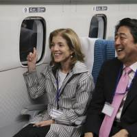 U.S. Ambassador to Japan Caroline Kennedy shares smiles with Prime Minister Shinzo Abe aboard a magnetically levitated train during a test run in Yamanashi Prefecture on Saturday. | AP