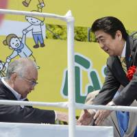Prime Minister Shinzo Abe and Nobuaki Koga, head of the Japanese Trade Union Confederation (Rengo), shake hands Saturday at a May Day gathering in Tokyo. | KYODO