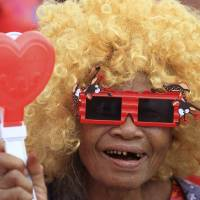 A pro-government Red Shirt member takes part in a rally in Bangkok on Saturday. Supporters of beleaguered Thai Prime Minister Yingluck Shinawatra held a major rally aimed at countering months of anti-government protests and an increasing spate of legal challenges that could bring down her administration. | AP