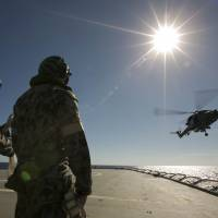 A helicopter leaves the flight deck of HMAS Success on Sunday as it completes a replenishment at sea with the Royal Malaysian Navy frigate KD Lekiu during the search for missing Malaysia Airlines Flight MH370 in the southern Indian Ocean.   DAVID CONNOLLY/CPOIS/AUSTRALIAN DEFENCE/AFP-JIJI