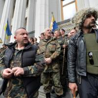Maidan self-defense activists guard the Ukrainian Parliament in Kiev during a session Tuesday as protesters outside the building demand that authorities take action against separatism in the eastern part of the country. | AFP