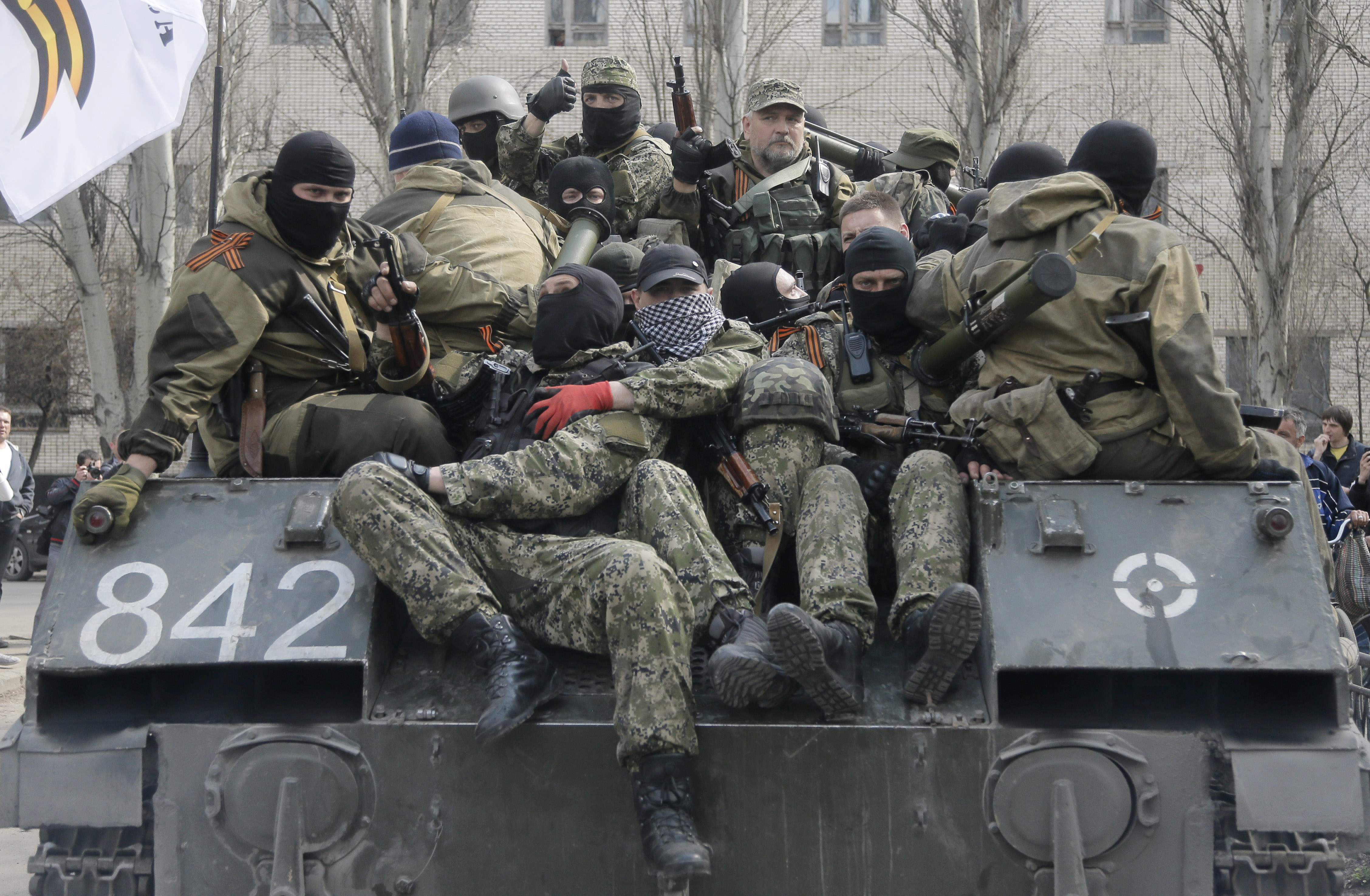 A combat vehicle with pro-Russian gunman on top runs through downtown Slovyansk, eastern Ukraine, on Wednesday. The troops on those vehicles wore green camouflage uniforms, had automatic weapons and grenade launchers and at least one had the St. George ribbon attached to his uniform, which has become a symbol of the pro-Russian insurgency in the area. | AP