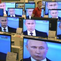 An employee walks past TV screens in an electronics store in Moscow showing President Vladimir Putin's televised question and answer session with the nation on Thursday.   AFP-JIJI