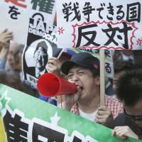 A protester voices his opposition to reinterpreting Article 9 of the Constitution in Tokyo on Thursday. | REUTERS