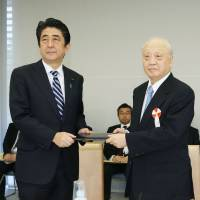 Shunji Yanai, chair of the Article 9 advisory panel, delivers a report on collective self-defense to Prime Minister Shinzo Abe on Thursday at the Prime Minister's Official Residence. | KYODO