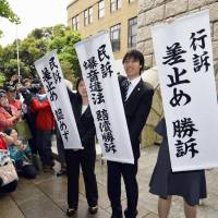 Plaintiffs and their supporters rejoice in Yokohama on Wednesday as lawyers hold up signs about a Yokohama District Court ruling that ordered the Self-Defense Forces to suspend nighttime flights at the Atsugi base in Kanagawa Prefecture. | KYODO