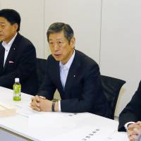 Liberal Democratic Party Vice President Masahiko Komura (second from right) speaks Tuesday during the second round of talks by the ruling coalition over revamping the nation's defense procedures.   KYODO