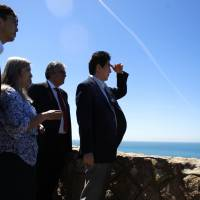 Prime Minister Shinzo Abe shades his eyes during a visit to Roca Cape — the westernmost point in continental Europe — near Sintra, Portugal, on Saturday as part of a six-country tour. | AP