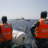 Vietnamese personnel monitor a Chinese Coast Guard vessel in the South China Sea on May 15. | REUTERS