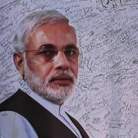 Signatures in support of BJP leader Narendra Modi are seen scrawled on a poster of him at party headquarters in New Delhi on Friday. | REUTERS