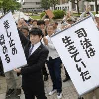 Lawyers hold signs reading 'justice is alive' and 'suspension has been ordered' at the Fukui District Court on Wednesday. | KYODO