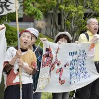 People against restarting reactors at the Oi nuclear power plant stage a protest Thursday outside Kansai Electric Power Co.'s headquarters in the city of Osaka. | KYODO