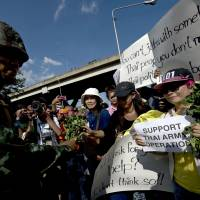 A Thai soldier receives roses from activists to show support for the Thai military at the Army Club in Bangkok on Friday. | AFP-JIJI