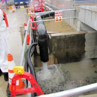Water is pumped into a drainage ditch at the Fukushima No. 1 plant on Wednesday. | TEPCO/ KYODO