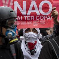 A masked protester holds a banner that reads in Portuguese, 'There won't be a Cup,' in reference to FIFA's 2014 World Cup, during a demonstration against money spent on the preparations for the international soccer tournament, in Sao Paulo on Saturday. | AP