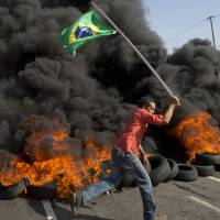 A member of the Homeless Workers Movement carries a Brazilian flag past burning tires during a May 15 protest against the money spent on the World Cup near Sao Paulo's Itaquerao stadium, which will host the soccer tournament's first match. | AP