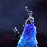 Above it all: Yang Liping towers archly over a foul crow as she gorgeously dances the star role in her current production, 'The Peacock.'