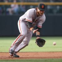 Looking it in: San Francisco shortstop Brandon Crawford fields a ground ball against Colorado in the first inning on Wednesday. The Giants downed the Rockies 5-1. | AP
