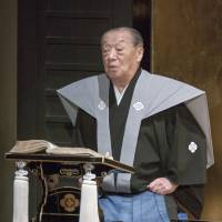Spoken art: Takemoto Sumitayu VII sits at an onstage lectern as he narrates a bunraku play. | COURTESY OF THE NATIONAL THEATRE, TOKYO