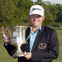 Long time coming: J.B. Holmes poses with the trophy after his win at the Wells Fargo Championship on Sunday.   AP