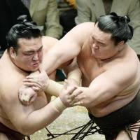 Back in the top spot: Yokozuna Hakuho outmuscles Kisenosato on Thursday to improve to 11-1 and regain the lead at the Summer Grand Sumo Tournament. | KYODO