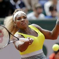 Ousted: Serena Williams plays a shot from Garbine Muguruza in a second-round match at the French Open on Wednesday. | REUTERS
