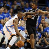 Surge protector: Thunder forward Serge Ibaka (left) competes against the Spurs' Boris Diaw during the fourth quarter of Game 3 of the Western Conference finals in a photo provided by USA Today on Sunday. The Thunder won 106-97.   REUTERS