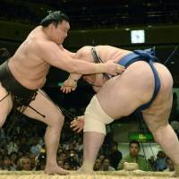 A day's work: Yokozuna Hakuho defeats Aoiyama on Tuesday at the Summer Grand Sumo Tournament. | KYODO