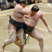 Another victory: Yokozuna Hakuho (right) works to send Aminishiki to a defeat on Friday at Ryogoku Kokugikan. | KYODO