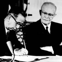 Prime Minister Nobusuke Kishi signs a treaty of mutual security in front of U.S. President Dwight Eisenhower in January 1960. The Japanese Defense Agency concluded in 1995 it was better to rely on the U.S. nuclear umbrella than develop its own nuclear weapons. | KYODO