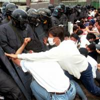 Students in Gwangju push riot police during an anniversary rally on May 19, 1996. | AP