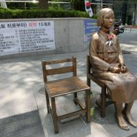 Cold comfort: A statue has been erected across from the Japanese Embassy in Seoul to honor the 'comfort women' who were recruited to serve in wartime military brothels during the 1930s and '40s. | JEFF KINGSTON