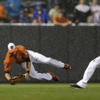 Slick play: Baltimore's David Lough (left) falls after catching a fly ball and colliding with teammate Manny Machado against Houston on Saturday. The Orioles edged the Astros 5-4.   AP
