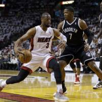 Into the paint: Miami's Dwyane Wade drives on Brooklyn's Joe Johnson in Game 1 Tuesday. The Heat routed the Nets 107-86. | AP