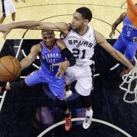 Towering figure: San Antonio's Tim Duncan defends as Oklahoma City's Russell Westbrook goes up for a shot in Game 1. | AP